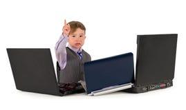 Un pequeño niño pequeño que trabaja en los ordenadores portátiles. Fotografía de archivo