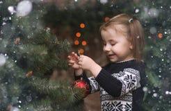 Un pequeño niño por el árbol del Año Nuevo Los niños adornan al Chris Imágenes de archivo libres de regalías
