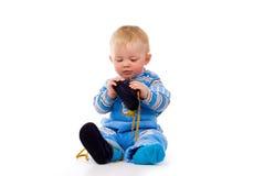Un pequeño niño que intenta vestir para arriba los zapatos imagen de archivo libre de regalías