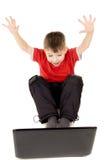 Un pequeño niño que mira feliz en el ordenador portátil, aumento Foto de archivo libre de regalías