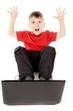 Un pequeño niño que mira feliz en el ordenador portátil, aumento Foto de archivo
