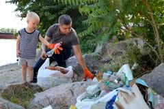 Un pequeño niño recoge basura en la playa Su papá señala su finger donde lanzar la basura Los padres enseñan los niños a limpieza imágenes de archivo libres de regalías