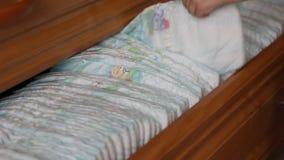 Un pequeño niño saca un pañal del bebé del aparador, primer metrajes