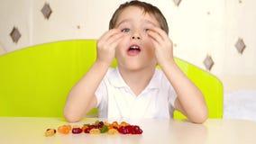 Un pequeño niño se está sentando en la tabla en el cuarto y está comiendo el caramelo gomoso brillante Un niño experimenta emocio almacen de video