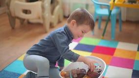 Un pequeño niño se sienta en el piso y los juegos con una variedad de animales metrajes