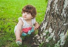 Un pequeño niño se sienta en la hierba cerca del árbol Foto de archivo libre de regalías
