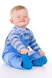 Un pequeño niño se sienta y ríe imagenes de archivo