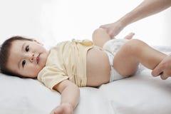 Un pequeño pañal samile del cambio del bebé aislado en blanco Fotografía de archivo