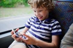 Un pequeño pasajero de un autobús de la ciudad con un smartphone a disposición Imagenes de archivo