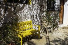 Un pequeño patio con un banco de madera amarillo y una silla de mimbre y potes con las plantas en la ciudad vieja de Finestrat Es foto de archivo libre de regalías