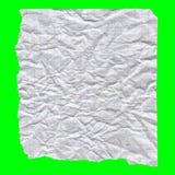 Un pequeño pedazo de documento arrugado y rasgado sobre fondo verde Fotografía de archivo