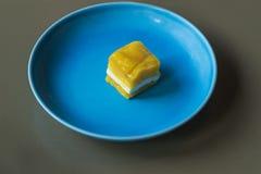 Un pequeño pedazo de torta amarilla en una placa azul El postre amarillo en un azul plat imágenes de archivo libres de regalías