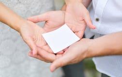 Un pequeño pedazo en blanco de Libro Blanco descansa en las palmas de hombres y imagen de archivo