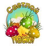 Un pequeño pollo amarillo en una corbata de lazo, tres huevos adornados con un modelo y las tortas de Pascua con las velas Imagen de archivo libre de regalías