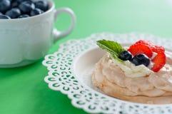 Un pequeño postre de Pavlova del merengue con la fresa y la menta foto de archivo