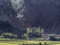 Un pequeño pueblo de montaña, en las rocas coloca un monasterio budista, iluminado por la luz, en el pie de campos verdes y del a Foto de archivo