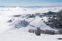Un pequeño pueblo en el top de una montaña nevosa en las nubes imagen de archivo libre de regalías