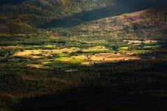 Un pequeño pueblo en un valle rodeado por el bosque y las montañas imagen de archivo libre de regalías