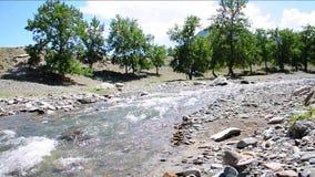 Un pequeño río tempestuoso Yaloman de la montaña, da vuelta a su curso en las orillas rocosas metrajes