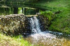 Un pequeño río y una cascada artificial en las rocas imagen de archivo libre de regalías