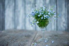 Un pequeño ramo de nomeolvides en un cristal en un fondo borroso de los tableros pintados con la pintura azul y algunas flores o fotografía de archivo libre de regalías
