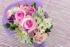 Un pequeño ramo de rosas miniatura bastante rosadas en backgr rayado fotografía de archivo