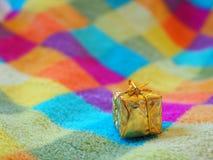 Un pequeño regalo de la Navidad en una manta a cuadros coloreada foto de archivo