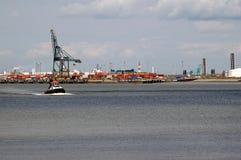 Un pequeño remolcador delante de un puerto enorme Fotos de archivo