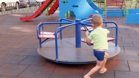 Un pequeño travieso círculo del muchacho el carrusel de los niños Juegos de niños en el patio en un día de verano soleado almacen de video