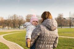 Un pequeño vistazo del ` s del niño de detrás su parte posterior del ` s de la madre imagenes de archivo