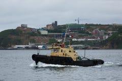 Un peque?o barco remolcador est? en el agua tranquila fotos de archivo