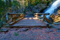 Un peque?o puente delante de una cascada imagenes de archivo