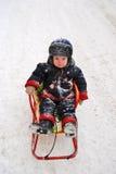 Un pequeño niño en el trineo Fotografía de archivo