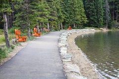 Un percorso ha allineato con i banchi di legno da una riva del lago Fotografie Stock