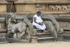 Un peregrino al Kelaniya Raja Maha Vihara cerca de Colombo en Sri Lanka se sienta en los pasos al cuarto de la capilla imagen de archivo libre de regalías