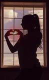 Un perfil de la muchacha que está haciendo una pausa la ventana y está haciendo el corazón con sus manos Humor romántico Puesta d Foto de archivo libre de regalías