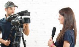 Un periodista de la mujer joven y un cameraman Imagenes de archivo
