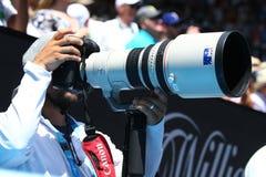Un periodista fotográfico utiliza un teleobjetivo de Canon para capturar la acción en Abierto de Australia 2016 foto de archivo