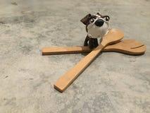 Un perro se está colocando en la cuchara y la bifurcación Foto de archivo libre de regalías