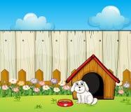 Un perro y la casa de perro dentro de la cerca Imagenes de archivo