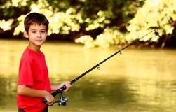 Un pescado de cogida del muchacho fotografía de archivo