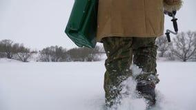 Un pescador camina en un lago nevado en busca de un buen lugar pesquero almacen de metraje de vídeo