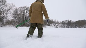 Un pescador camina en un lago nevado en busca de un buen lugar pesquero metrajes