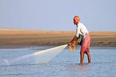 Un pescador coge pescados por la red tradicional de la mano en la India Foto de archivo libre de regalías