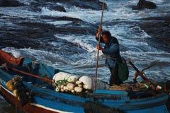 Un pescador con su barco Foto de archivo