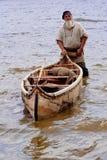 Un pescador con su bote pequeño. Fotografía de archivo