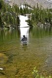 Un pescador de la mosca se coloca en el agua de un lago glacial Foto de archivo libre de regalías