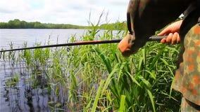 Un pescador de la orilla del lago está pescando, pesca tranquila almacen de metraje de vídeo