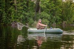 Un pescador en un barco Fotos de archivo