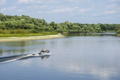 Un pescador en un barco de motor monta el río Imagenes de archivo